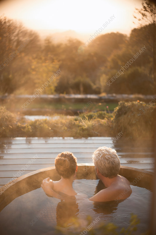 Serene couple in hot tub with autumn view