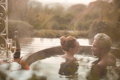 Couple talking soaking in hot tub with champagne