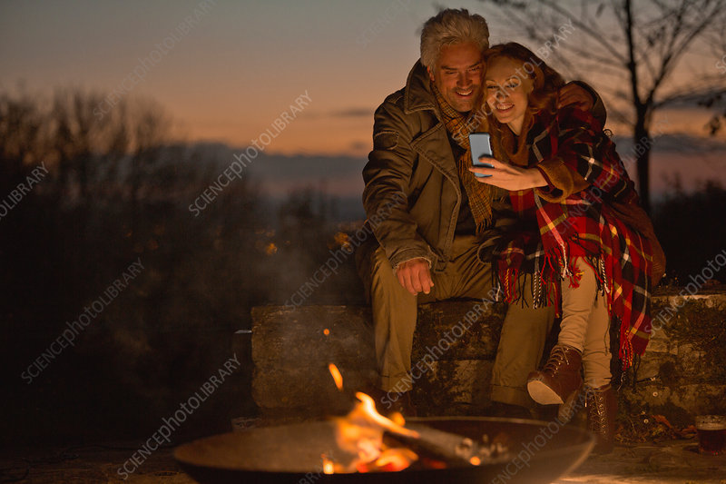 Couple using cell phone at autumn carefree