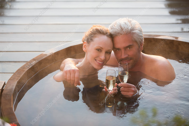 Portrait couple drinking champagne in hot tub