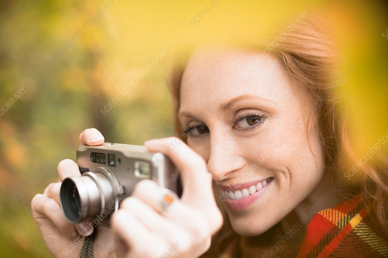 Woman using digital camera among autumn leaves