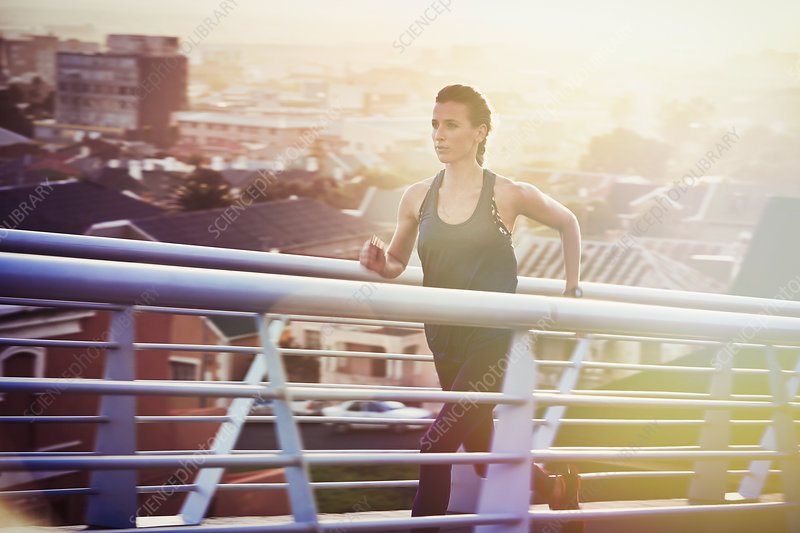 Female runner running up urban footbridge