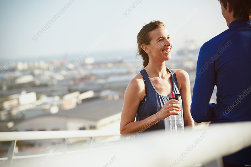 Smiling runner couple resting drinking water