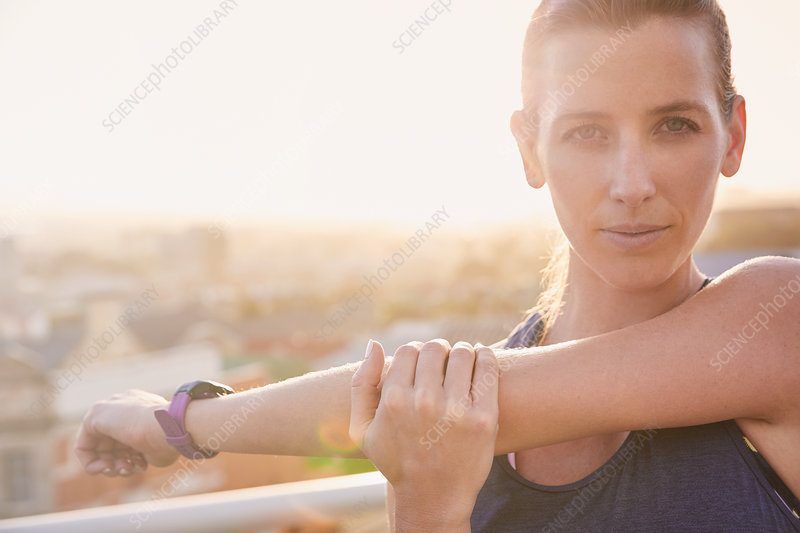 Portrait female runner stretching arms