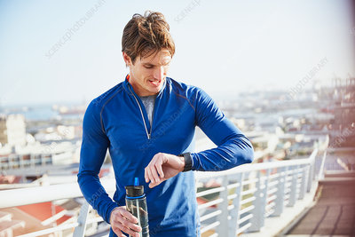 Male runner resting and drinking water