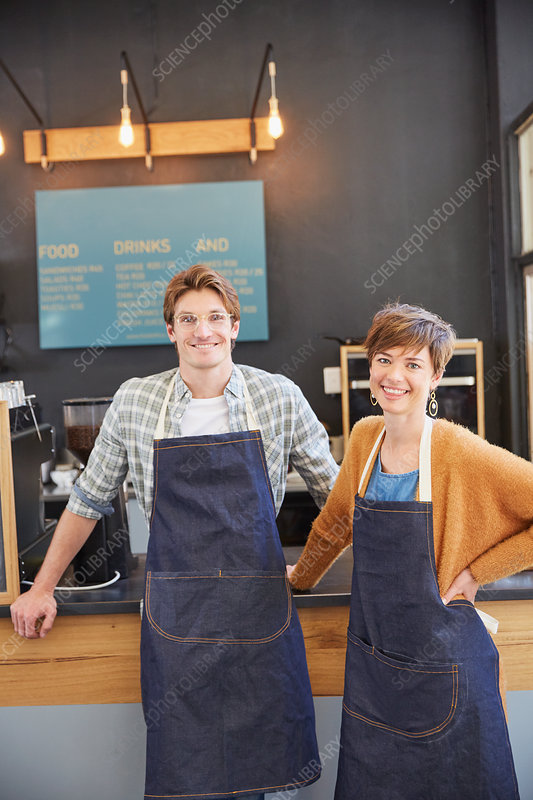 Portrait smiling cafe owners wearing denim aprons