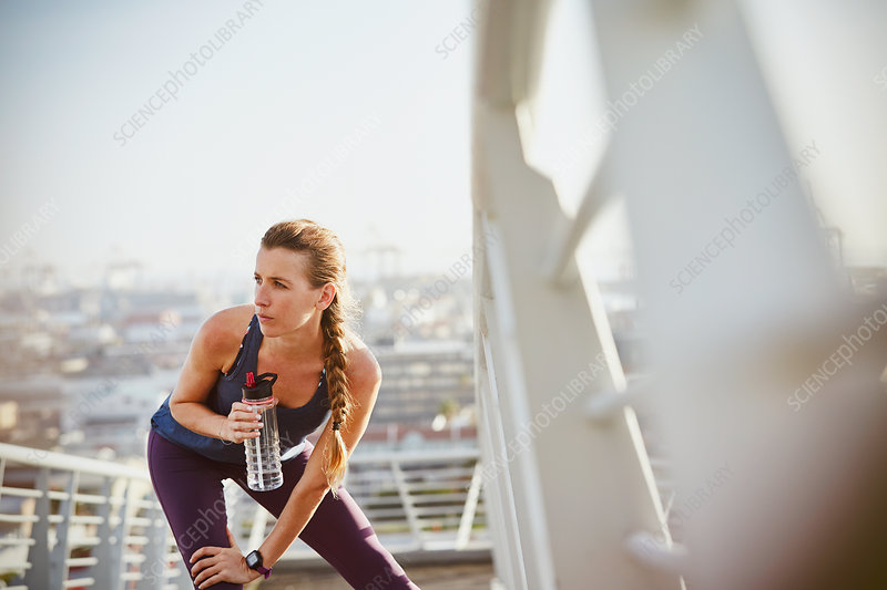 Female runner stretching leg and drinking water