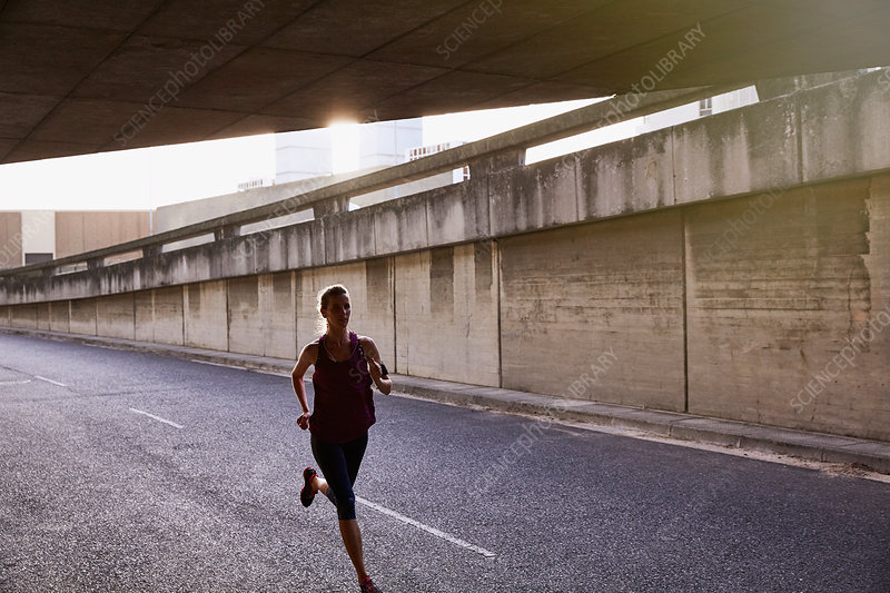 Female runner running into urban tunnel