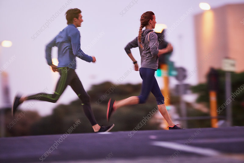 Runner couple running on urban city street