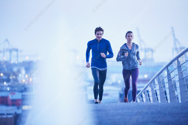 Runner couple running on urban footbridge at dawn
