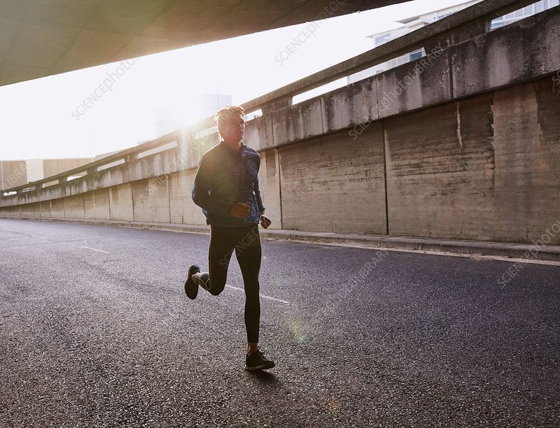 Male runner running on urban street into tunnel
