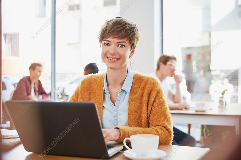 Portrait smiling businesswoman working at laptop
