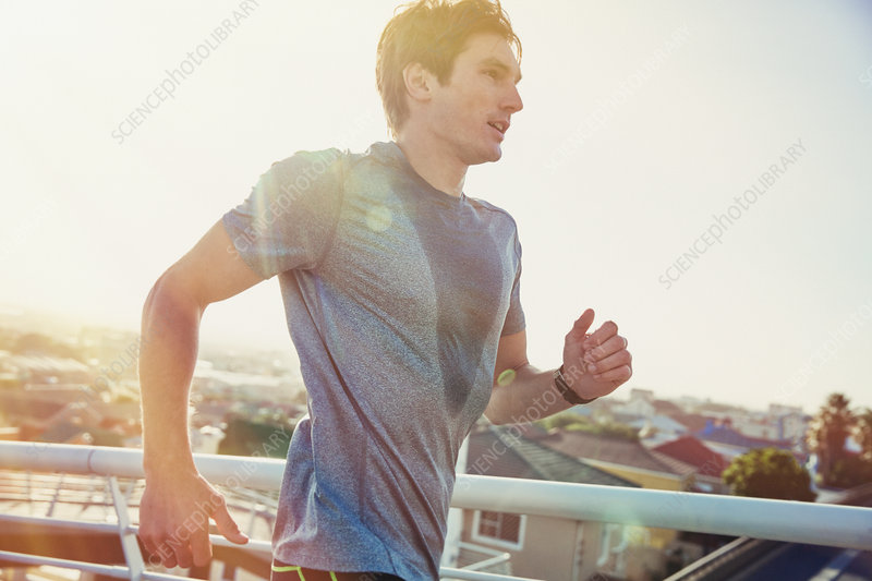 Sweaty male runner running at sunrise