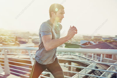 Determined male runner running at sunrise