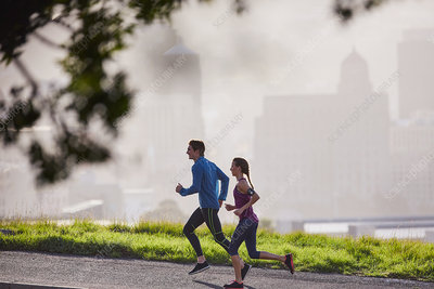 Runner couple running on sunny urban city street