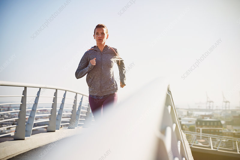 Female runner running on sunny urban footbridge