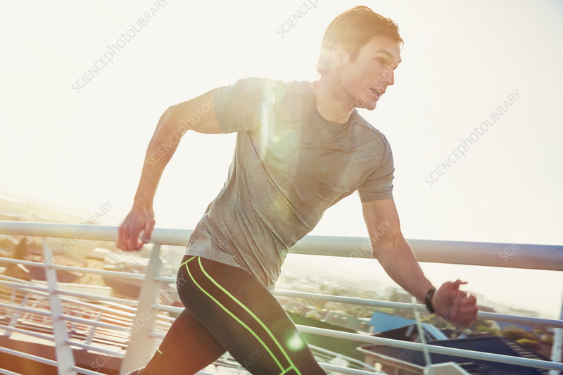 Determined male runner running on sunny footbridge