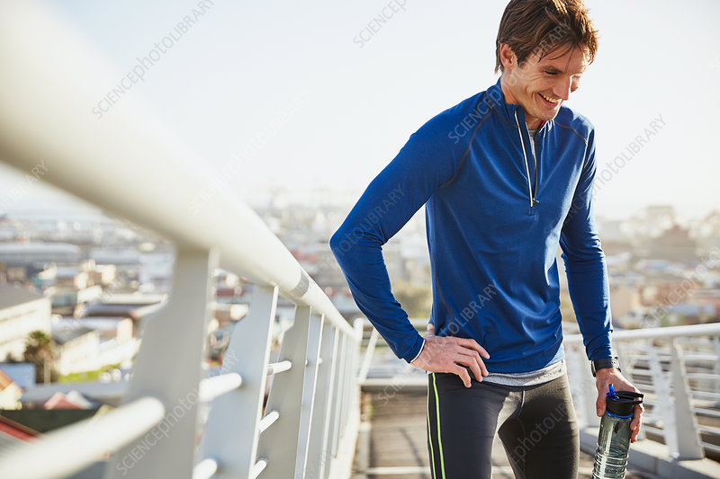 Smiling male runner resting drinking water
