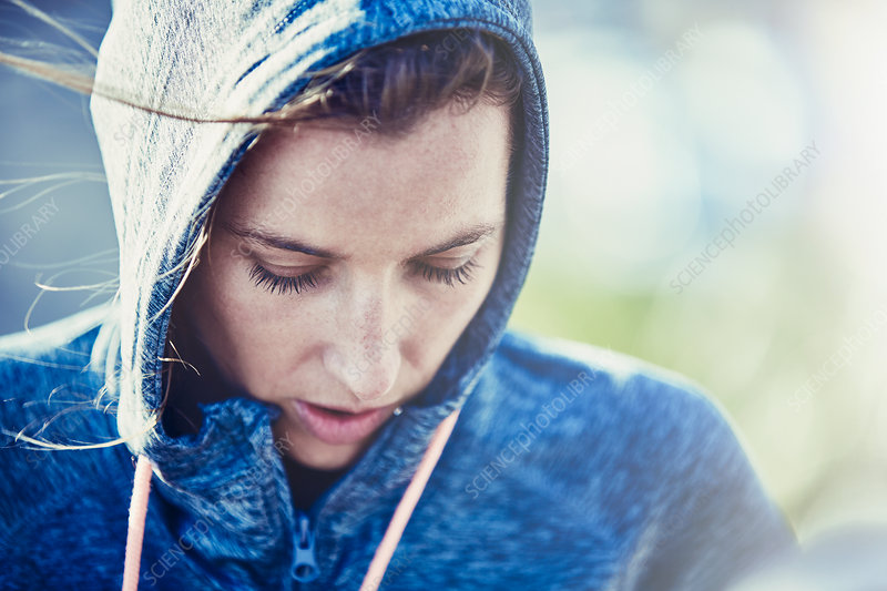 Close up female runner in hoody looking down