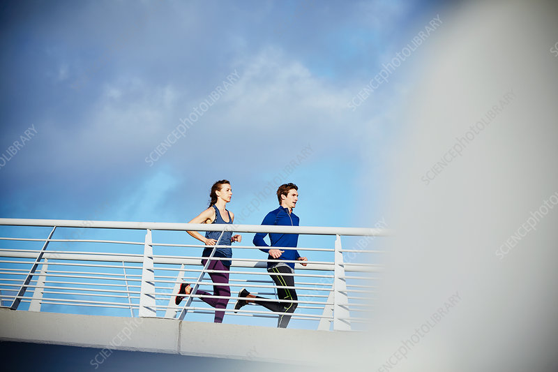 Runner couple running on sunny footbridge
