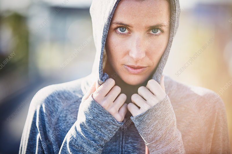 Portrait serious female runner wearing hoody