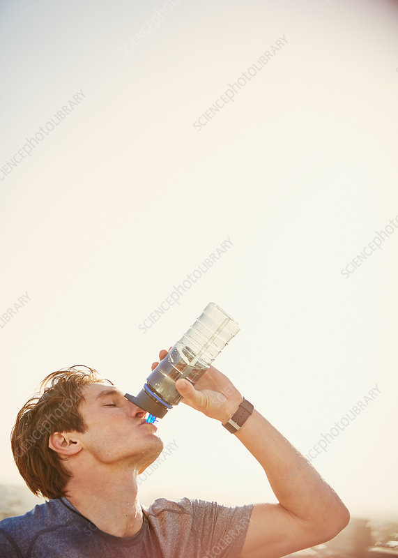 Thirsty male runner drinking water