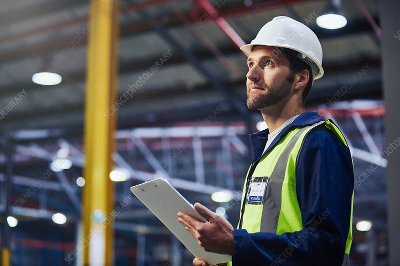 Worker with clipboard looking up