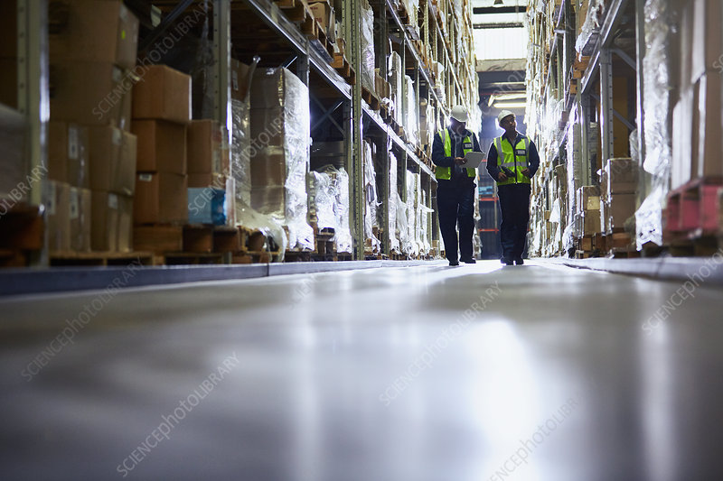 Workers walking in distribution warehouse aisle