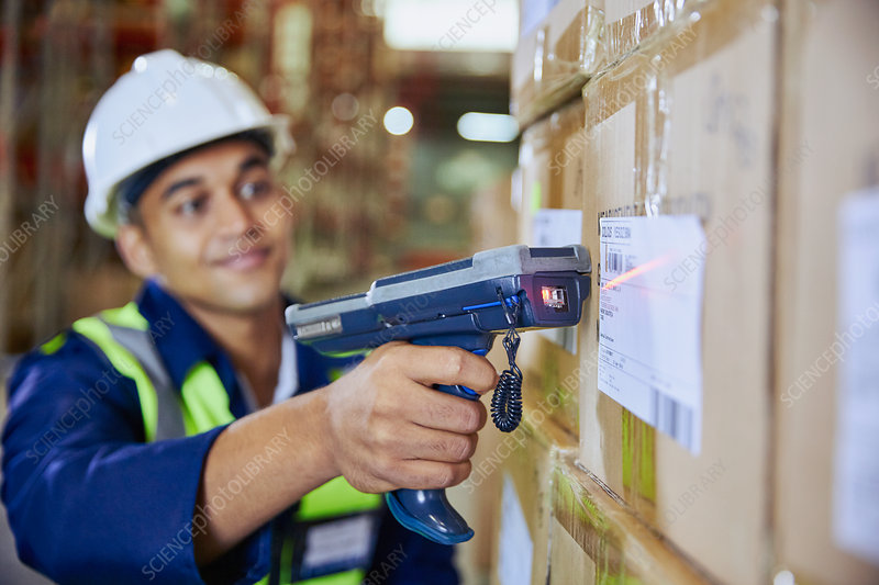 Worker with scanner scanning barcode on box