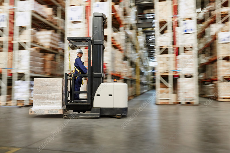 Worker operating forklift moving pallet of boxes