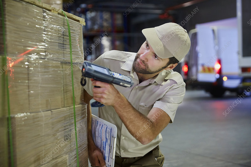 Truck driver worker scanning pallet of boxes