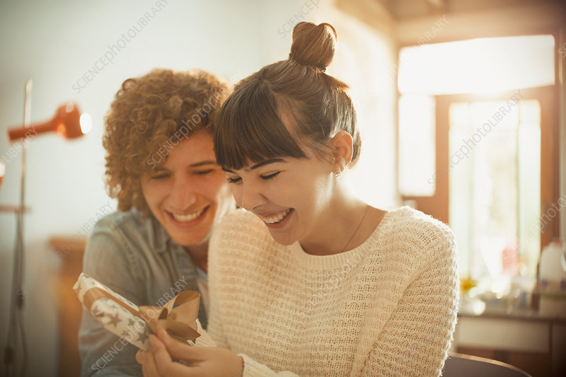 Smiling young couple opening birthday gift
