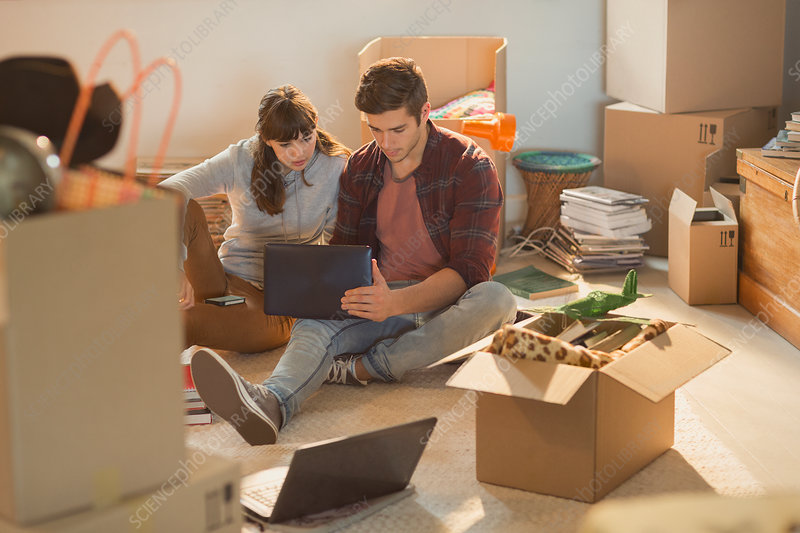 Young couple surrounded by moving boxes