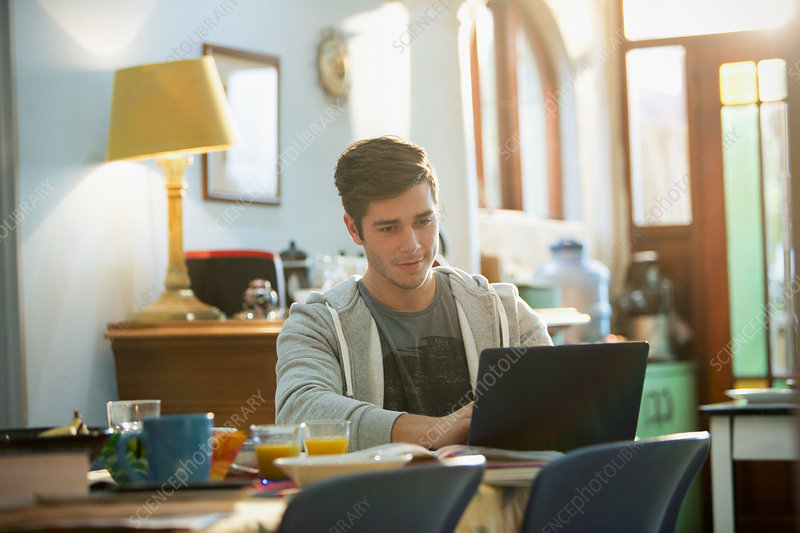 Young man college student studying at laptop