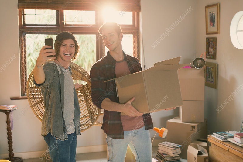Young men taking selfie moving boxes in apartment