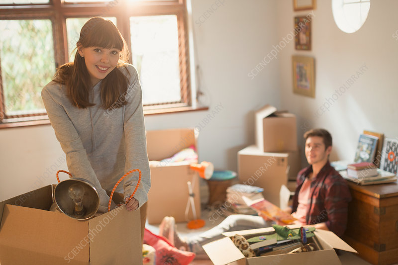Young couple unpacking moving boxes in apartment