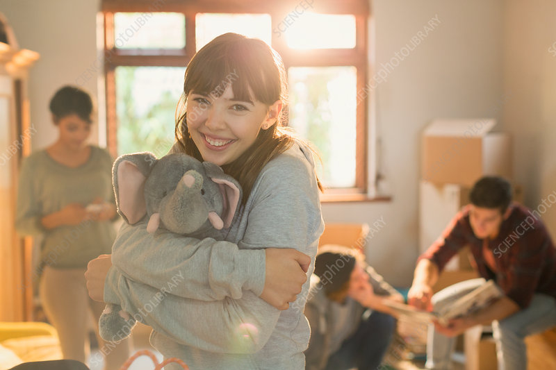 Young woman hugging stuffed elephant