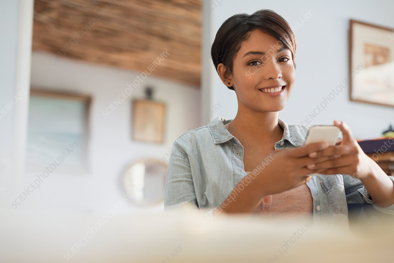 Portrait smiling young woman using cell phone