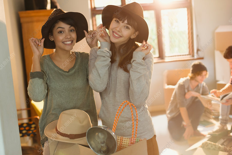 Women friends trying on hats moving into apartment