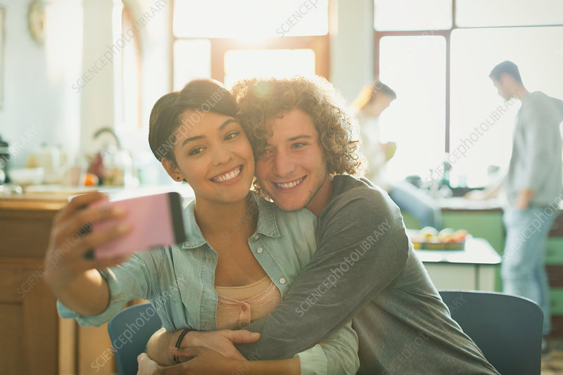 Smiling affectionate young couple taking selfie