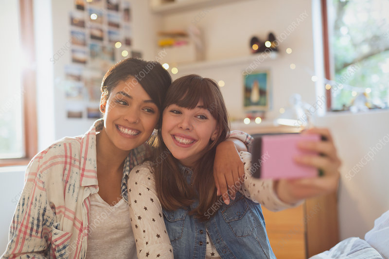 Enthusiastic young women friends taking selfie