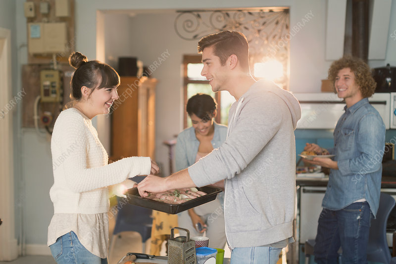 Young couples roommates cooking in kitchen