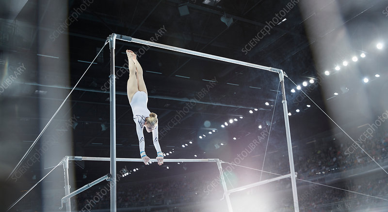 Female gymnast performing on uneven bars in arena
