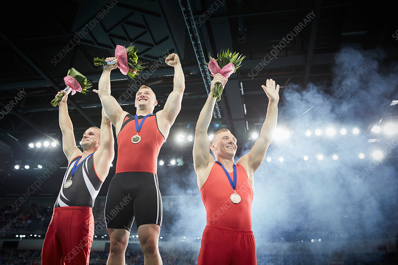 Male gymnasts cheering on winners podium