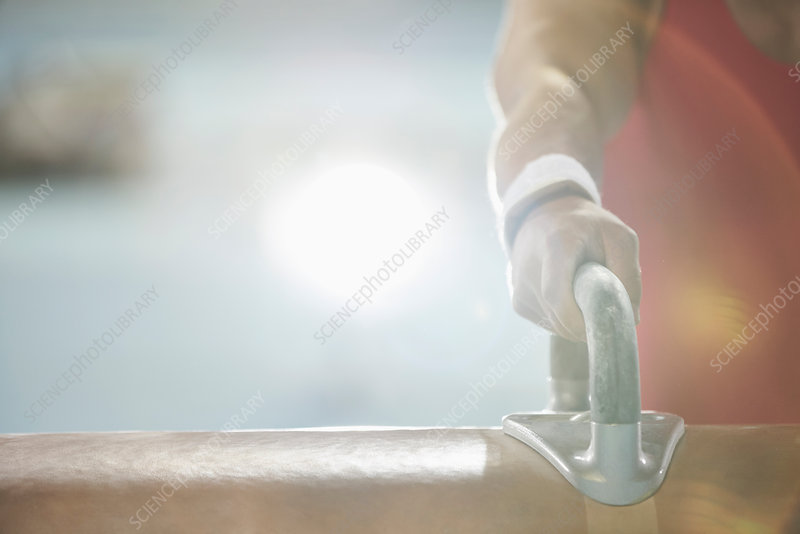 Close up hand of male gymnast on pommel horse