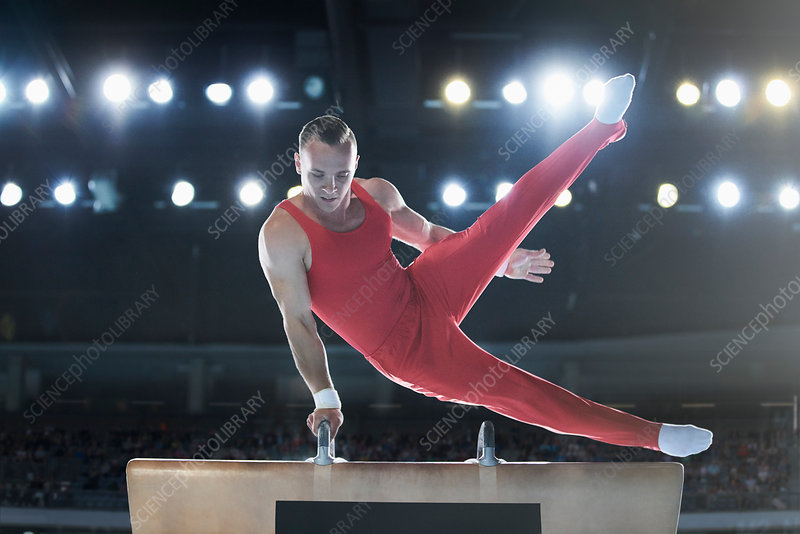 Male gymnast performing on pommel horse in arena