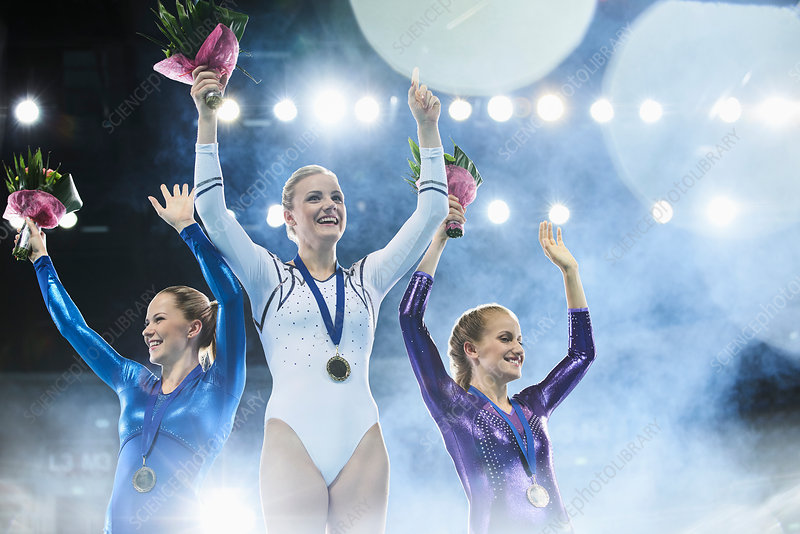 Female gymnasts waving on winners podium