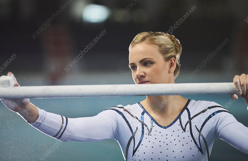 Female gymnast chalking uneven bars