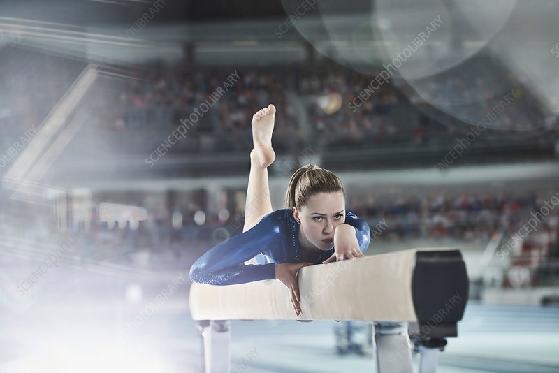 Female gymnast practicing on balance beam in arena