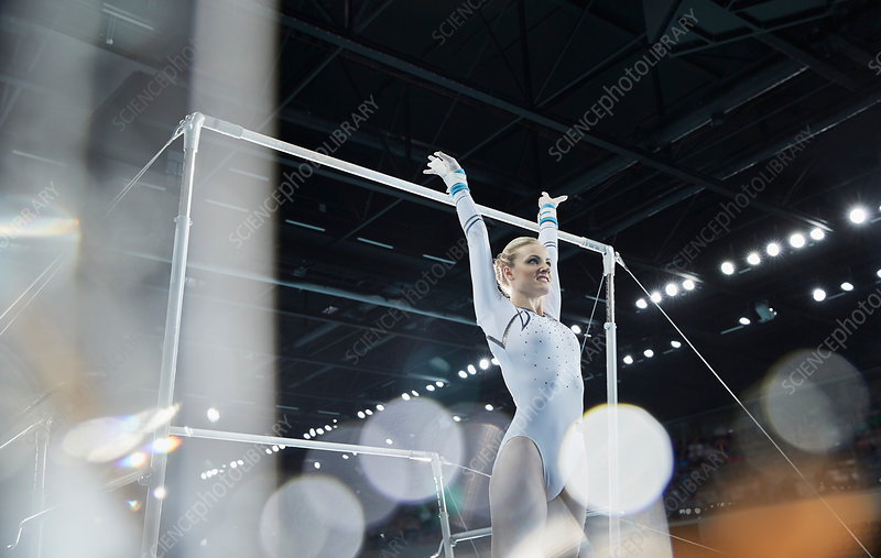 Female gymnast with arms raised below uneven bars